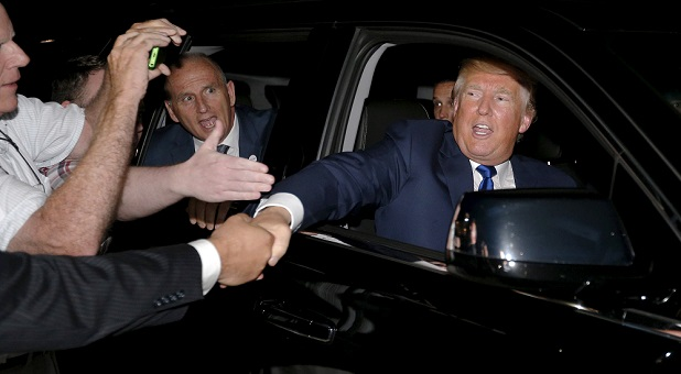U.S. Republican presidential candidate Donald Trump shakes hands with supporters as he is driven away following a campaign town hall meeting in Derry, New Hampshire